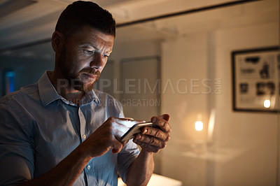 Buy stock photo Shot of a mature businessman using a cellphone while working late in an office