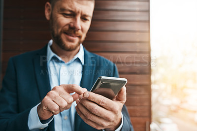 Buy stock photo Shot of a mature businessman using his cellphone on the office balcony