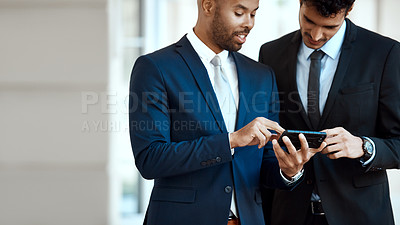 Buy stock photo Cropped shot of unrecognizable businessmen using a cellphone together outside