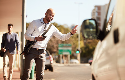 Buy stock photo Cropped shot of a handsome young businessman hailing a ride in the city
