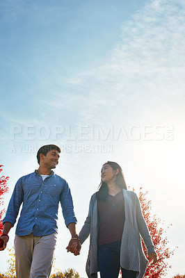 Buy stock photo Shot of a loving young couple out for a walk in the park