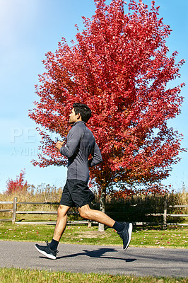 Buy stock photo Shot of a sporty young man running outdoors