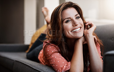 Buy stock photo Shot of an attractive young woman relaxing on the sofa at home