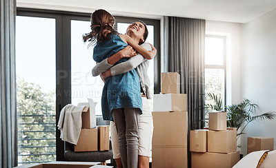 Buy stock photo Cropped shot of an attractive young woman and her daughter dancing while moving into their new home