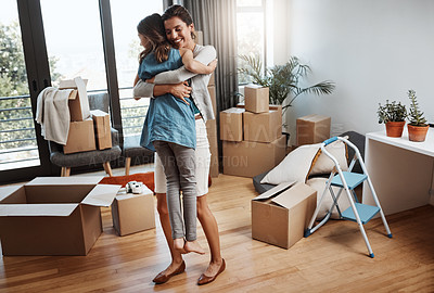 Buy stock photo Full length shot of an attractive young woman and her daughter dancing while moving into their new home