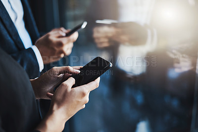 Buy stock photo Closeup shot of two unrecognizable businesspeople using their cellphones in an office
