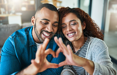 Buy stock photo Shot of a young couple making a heart gesture with their hands outdoors