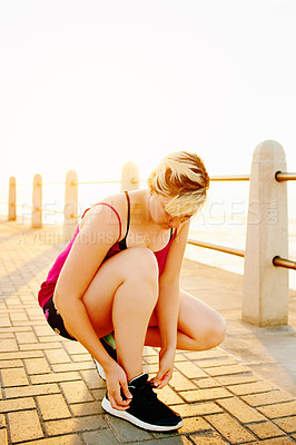 Buy stock photo Shot of an attractive young woman tying her shoelaces on the promenade