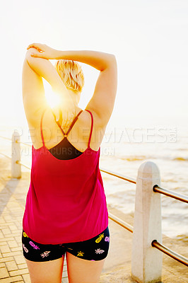 Buy stock photo Rearview shot of an unrecognizable woman working out on the promenade