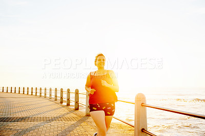 Buy stock photo Cropped shot of an attractive young woman running on the promenade
