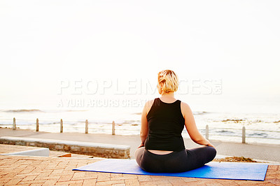 Buy stock photo Rearview shot of an unrecognizable woman practising yoga on the promenade at the beach