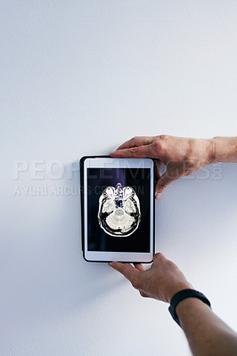 Buy stock photo Cropped shot of an unrecognizable male doctor holding a tablet displaying an MRI scan against a grey background