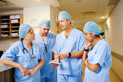 Buy stock photo Cropped shot of a team of doctors looking at a tablet while standing in a hospital
