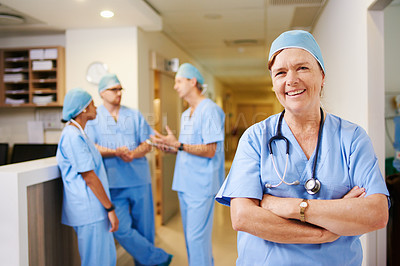 Buy stock photo Cropped portrait of a mature female doctor standing with her arms folded and her team in the background