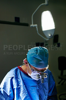 Buy stock photo Cropped shot of a male doctor performing surgery in the operating room