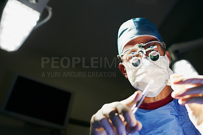 Buy stock photo Low angle shot of a male doctor performing surgery in the operating room