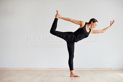 Buy stock photo Shot of a focused young woman practicing yoga poses inside of a studio during the day