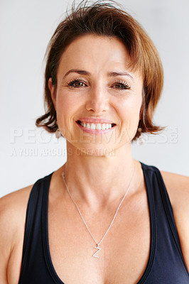 Buy stock photo Portrait of a cheerful middle aged woman wearing yoga clothes before a session inside of a studio