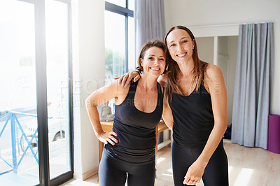 Buy stock photo Portrait of two cheerful young women standing arms in arms just before a yoga session inside of a studio