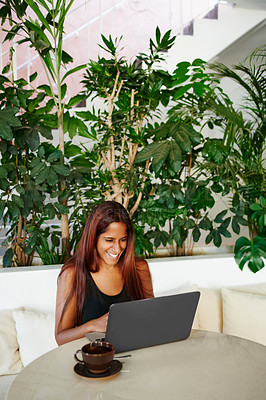 Buy stock photo Cropped shot of a beautiful young woman using her laptop in a cafe
