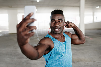 Buy stock photo Shot of a sporty young man taking selfies with a mobile phone while working out in an underground parking lot