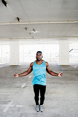 Buy stock photo Shot of a handsome and sporty young man working out with a skipping rope in an underground parking lot