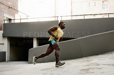 Buy stock photo Shot of a handsome and sporty young man going for a run in and around the city