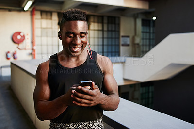 Buy stock photo Shot of a sporty young man using a mobile phone during his workout out in an urban apartment block