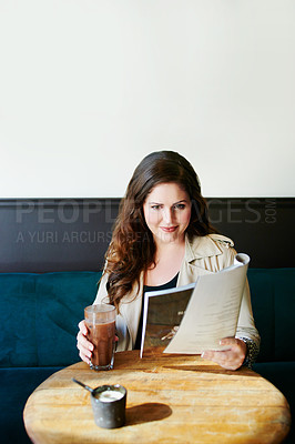 Buy stock photo Shot of a young woman reading a magazine in a cafe