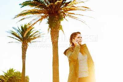 Buy stock photo Cropped shot of a beautiful young woman on a call while spending the day on the promenade at the beach