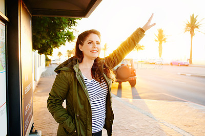 Buy stock photo Cropped shot of a beautiful young woman hailing a cab outside