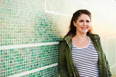 Buy stock photo Cropped shot of a beautiful young woman posing against a green wall outside