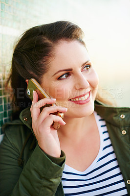 Buy stock photo Cropped shot of a beautiful young woman on a call against a green wall outside