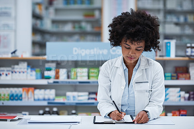 Buy stock photo Shot of a young pharmacist writing on a clipboard in a chemist