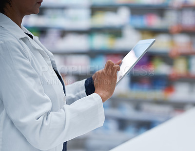 Buy stock photo Closeup shot of an unrecognizable pharmacist working on a digital tablet in a pharmacy