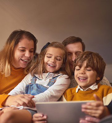 Buy stock photo Cropped shot of an affectionate young family of four using a digital tablet while sitting on the sofa at home