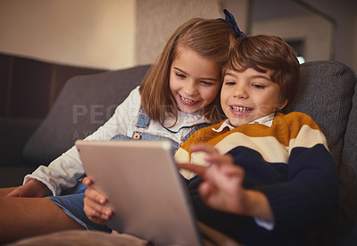 Buy stock photo Cropped shot of an adorable little boy and his older sister using a digital tablet while sitting on the sofa at home