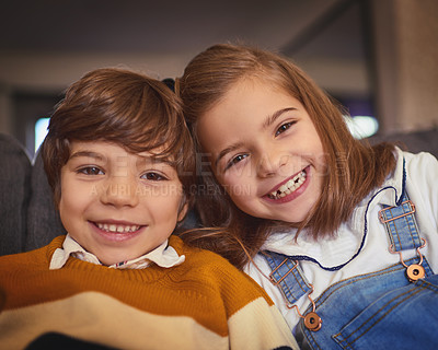Buy stock photo Cropped portrait of an adorable little boy and his older sister sitting on the sofa at home