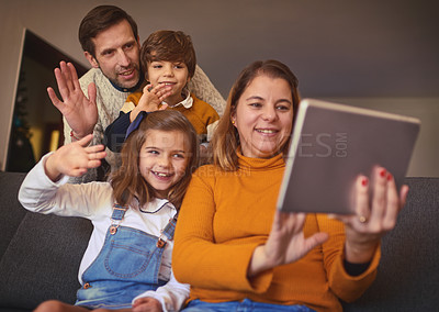 Buy stock photo Cropped shot of an affectionate young family of four video chatting using a digital tablet on the sofa at home