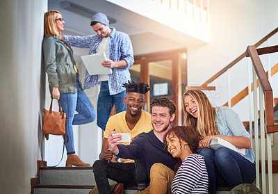 Buy stock photo Shot of a group of university students taking a selfie on the staircase at campus
