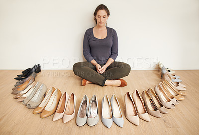 Buy stock photo Full length shot of an attractive young woman sitting on a wooden floor surrounded by high heels
