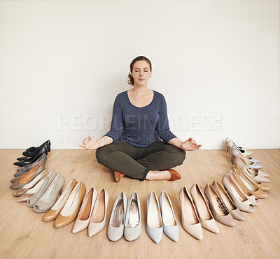 Buy stock photo Full length shot of an attractive young woman meditating on a wooden floor surrounded by high heels