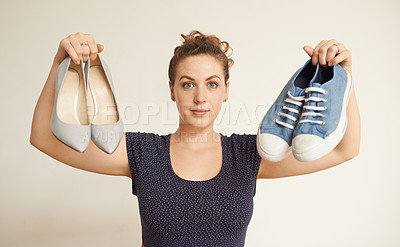 Buy stock photo Cropped portrait of an attractive young woman deciding between two pairs very different shoes
