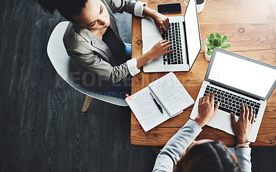 Buy stock photo High angle shot of two businesswomen working on laptops in an office