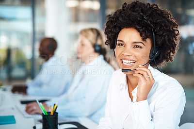 Buy stock photo Portrait of a young call centre agent working in an office with her colleagues in the background