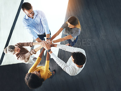 Buy stock photo High angle shot of a group of businesspeople standing in the office with their hands in a huddle