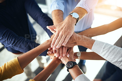 Buy stock photo High angle shot of a group of unrecognizable businesspeople standing in the office with their hands in a huddle