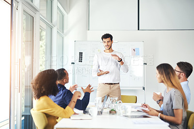 Buy stock photo Cropped shot of a handsome young businessman giving a presentation during a meeting in the boardroom