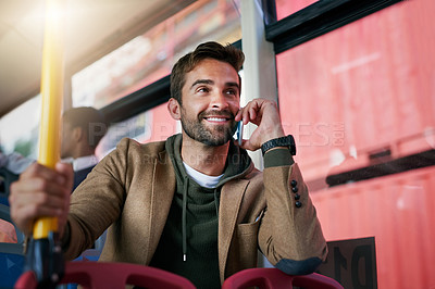 Buy stock photo Cropped shot of a handsome young man making a phonecall during his morning bus commute