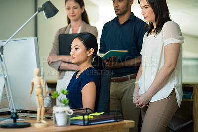 Buy stock photo Shot of a group of businesspeople working together on a computer in an office